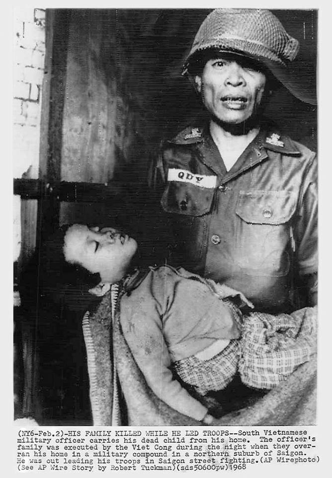 Major Quy holding dead child